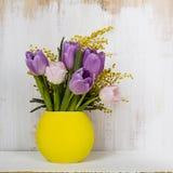 Ramalhete das tulipas em um vaso amarelo em um fundo de madeira Imagem de Stock Royalty Free