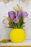 Ramalhete das tulipas em um vaso amarelo em um fundo de madeira Fotos de Stock