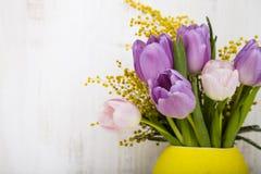 Ramalhete das tulipas em um vaso amarelo em um fundo de madeira Imagem de Stock