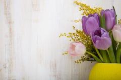 Ramalhete das tulipas em um vaso amarelo em um fundo de madeira Foto de Stock Royalty Free