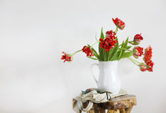 Ramalhete das tulipas no vaso branco na cadeira rústica de madeira Fotos de Stock Royalty Free