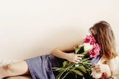 Ramalhete de cheiro da peônia do moderno feliz da mulher que encontra-se na cama no foto de stock