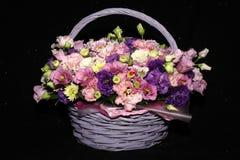 Ramalhete de flores cor-de-rosa e roxas em uma cesta de vime imagem de stock royalty free