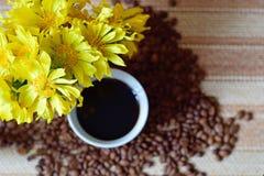 Ramalhete de flores do amarelo do prado Uma chávena de café na tabela imagens de stock