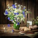 Ramalhete de flores do campo, de vidro do leite e do pão macio fotografia de stock royalty free