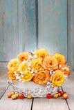 Ramalhete de rosas alaranjadas em uma cesta de vime branca Fotos de Stock Royalty Free