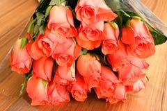 Ramalhete de rosas alaranjadas em uma tabela de madeira com reflexão Imagem de Stock