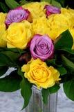 Ramalhete de rosas amarelas com roxo três no vaso de vidro Fotografia de Stock
