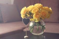 Ramalhete de rosas amarelas em um vaso redondo em uma tabela perto de um sofá Fotografia de Stock Royalty Free