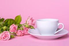 Ramalhete de rosas cor-de-rosa e um copo e uns pires brancos em um fundo cor-de-rosa Imagens de Stock