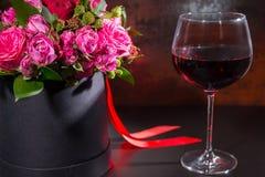 Ramalhete de rosas cor-de-rosa e vermelhas e da fita vermelha em um preto circular Imagens de Stock Royalty Free