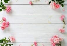 Ramalhete de rosas e do presente cor-de-rosa bonitos na embalagem cor-de-rosa no fundo de madeira branco Vista superior Copie o e fotos de stock royalty free