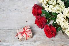 Ramalhete de rosas vermelhas com a caixa de presente no fundo de madeira imagem de stock