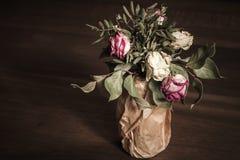 Ramalhete de rosas vermelhas e brancas secadas, baixa chave Foto de Stock