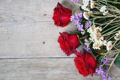 Ramalhete de rosas vermelhas no fundo de madeira imagem de stock