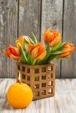 Ramalhete de tulipas alaranjadas, iluminado vela Fotografia de Stock