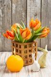 Ramalhete de tulipas alaranjadas, iluminado vela e coelhinhos da Páscoa Fotografia de Stock Royalty Free