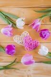 Ramalhete de tulipas cor-de-rosa macias com corações de vime em de madeira claro Imagem de Stock Royalty Free