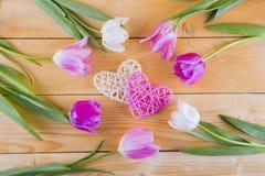 Ramalhete de tulipas cor-de-rosa macias com corações de vime em de madeira claro Fotos de Stock