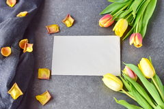 Ramalhete de tulipas rosados e amarelas em um fundo abstrato preto, com pétalas secas Espaço para o texto Conceito romance Foto de Stock Royalty Free