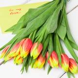 Ramalhete de tulipas vermelhas amarelas no fundo de madeira Fotos de Stock