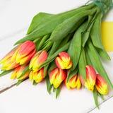 Ramalhete de tulipas vermelhas amarelas no fundo de madeira Foto de Stock