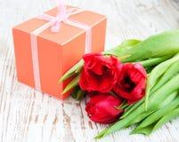 Ramalhete das tulipas, caixa de presente em uma tabela fotos de stock