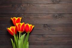 Ramalhete de tulipas vermelhas e amarelas em um fundo de madeira escuro A vista da parte superior imagem de stock