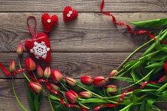Ramalhete de tulipas vermelhas e de três corações vermelhos em uma parte traseira de madeira velha Fotos de Stock Royalty Free