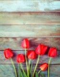 Ramalhete de tulipas vermelhas na luz - fundo retro de madeira azul do grunge com espaço da cópia Fotos de Stock Royalty Free