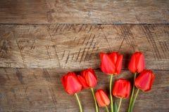 Ramalhete de tulipas vermelhas no fundo retro de madeira do grunge com espaço da cópia Imagens de Stock Royalty Free