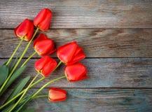 Ramalhete de tulipas vermelhas no fundo retro de madeira do grunge com espaço da cópia Imagem de Stock Royalty Free