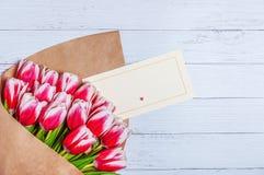 Ramalhete de tulipas vermelhas para o dia das mulheres do feriado e o dia de Valentim no fundo de placas de madeira fotos de stock royalty free