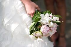 Ramalhete delicado do casamento com as peônias nas mãos da noiva imagens de stock