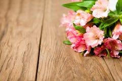 Ramalhete do alstroemeria cor-de-rosa na placa de madeira Fotos de Stock Royalty Free