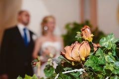Ramalhete do casamento com noiva e noivo no fundo Fotografia de Stock Royalty Free