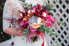 Ramalhete do casamento com tulipas, as bagas e as fitas cor-de-rosa nas mãos da noiva Fotografia de Stock