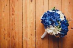 Ramalhete do casamento das flores azul-e-brancas no assoalho de madeira Fotografia de Stock