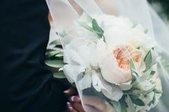 Ramalhete do casamento das peônias de creme nas mãos da noiva sob o véu fotos de stock