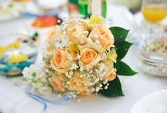 Ramalhete do casamento das rosas alaranjadas que encontram-se em uma tabela Imagens de Stock Royalty Free