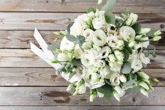 Ramalhete do casamento das rosas brancas e dos botões de ouro em uma tabela de madeira Vista superior Fundo rústico velho imagens de stock royalty free
