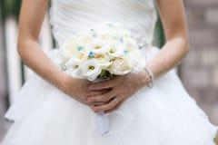 Ramalhete do casamento das rosas brancas na mão do ` s da noiva foto de stock royalty free