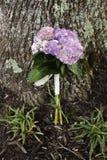 Ramalhete do casamento de encontro a uma árvore Imagem de Stock Royalty Free