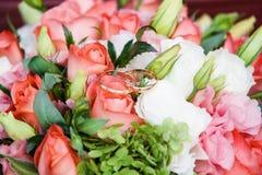 Ramalhete do casamento (flores cor-de-rosa) com alianças de casamento do ouro Fotografia de Stock