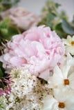 Ramalhete do casamento do lilás, das rosas, da peônia e do botão de ouro brancos em uma tabela de madeira Lotes das hortaliças, a imagem de stock royalty free