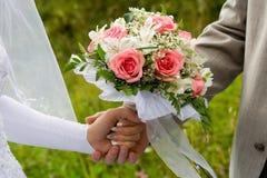 Ramalhete do casamento nas mãos Fotografia de Stock Royalty Free