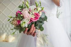 Ramalhete do casamento nas mãos das noivas foto de stock