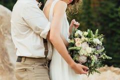 Ramalhete do casamento nas mãos do ` s da noiva fotografia de stock royalty free