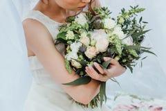 Ramalhete do casamento nas mãos do ` s da noiva foto de stock
