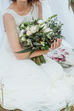 Ramalhete do casamento nas mãos do ` s da noiva imagem de stock royalty free